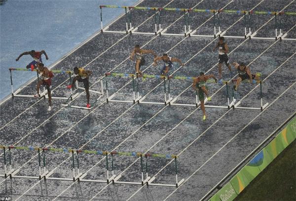 Cơn mưa xối xả không thể ngăn chặn những VĐV đua tranh nội dung 100m vượt rào.