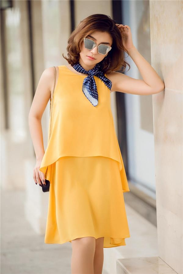 Người đẹp thích thú khi diện bộ váy màu vàng để chào đón mùa thu, điểm nhấn của bộ trang phục là chiếc khăn xinh xắn và mắt kính sành điệu.