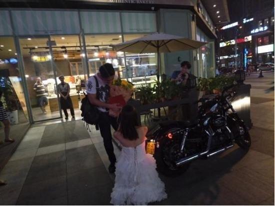 Cô gái xinh đẹp mặc váy cưới màu trắng, lài chiếc xe moto mà bạn trai hằng mơ ước đến trước trung tâm thương mại và quỳ xuống cầu hôn anh.