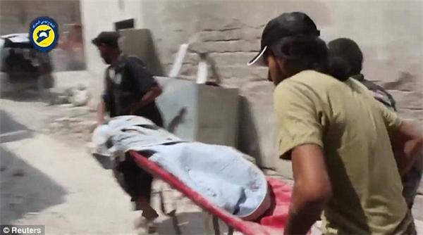 Chiếc nạng khiêng một thi thể nhỏ bé từ đống đổ nát của một tòa nhà.(Ảnh: Reuters)