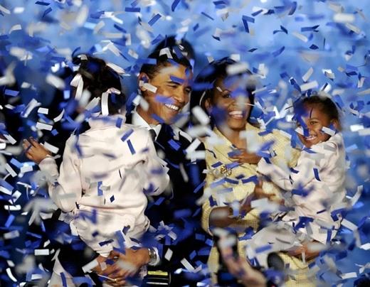 Barack Obama bế bé Malia và bà Michelle bế bé Sasha đang trong cơn mưa hoa giấy chúc mừng sau khi ông phát biểu nhận giải tại Chicago vào ngày 2 tháng 11 năm 2004.