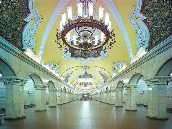 """Liên Bang Nga nổi tiếng với hệ thống tàu điện ngầm ấn tượng bậc nhất thế giới, đặc biệt ở Moscow. Nhà ga Komsomolskaya xứng đáng là một đại diện nổi bậccho """"cung điện tàu ngầm"""" khắp nước Nga. Nó được thiết kế theo phong cách tân cổ điển với những chiếc đèn chùm lộng lẫy khổng lồ, cộtbyzantine và bắt mắt với các họa tiết được chạm trổ tinh tế bằng tay trên trần nhà. Theo nhiều nguồn thông tin, nhà gaKomsomolskaya được kiến trúc sư Alexey Shchuevthiết kế nó như một hình ảnh minh họa cho bài phát biểu của Stalin vào năm 1941."""