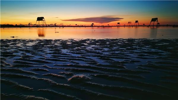 Buổi sớm khi nước biển rút đi để lộ những bãi cát trải dài mênh mông... Xa xa là Cồn Đen, Cồn Lu, Cồn Lặc..