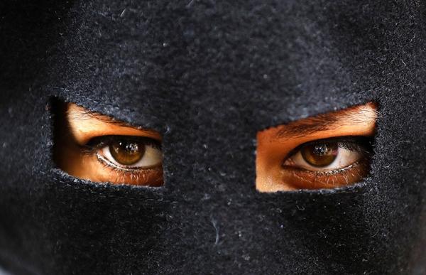 """Một nhà hoạt động đeo mặt nạ đang tham dựbữa tiệcburkinis """"mặc những gì bạn muốn bên bãi biển"""" bên ngoài đại sứ quán Phápở London.Cuộc biểu tình nhằmchống lại lệnh cấm củachính quyền Pháp đangđàn áp phụ nữ Hồi giáo mặc burkinis trên bãi biển."""