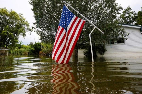 Một lá cờ Mỹ đang bị ngập một phầntrên dòng nước lũ nghiêm trọng ở Sorrento, Louisiana.