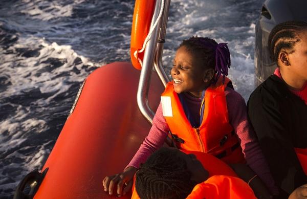 Một bé gáidi cư 9 tuổitên Sira đến từ Nigeria đang nởnụ cười hạnh phúctrên con tàu RIB của Tổ chức phi chính phủProactiva Open Arms, ở vùng biển Địa Trung Hải, khoảng 17 dặm về phía bắc Sabratah, Libya.