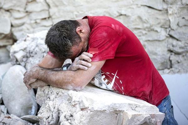 Một người đàn ông đangtựa vào đống đổ nát để giấu đi nỗi đau của mìnhsau trận động đất ở Amatrice.