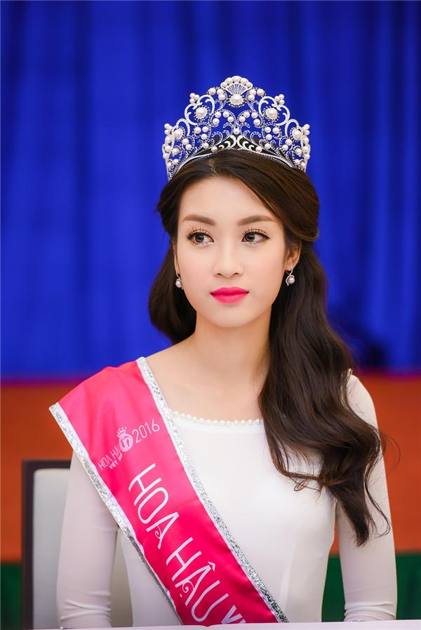 Hoa hậu Đỗ Mỹ Linh diện áo dài cổ thuyền có chi tiết ngọc trai đính kết đồng điệu với vương miện. Đỗ Mỹ Linh cao 1m71, sinh năm 1996 và đang là sinh viên Đại học Ngoại thương Hà Nội.