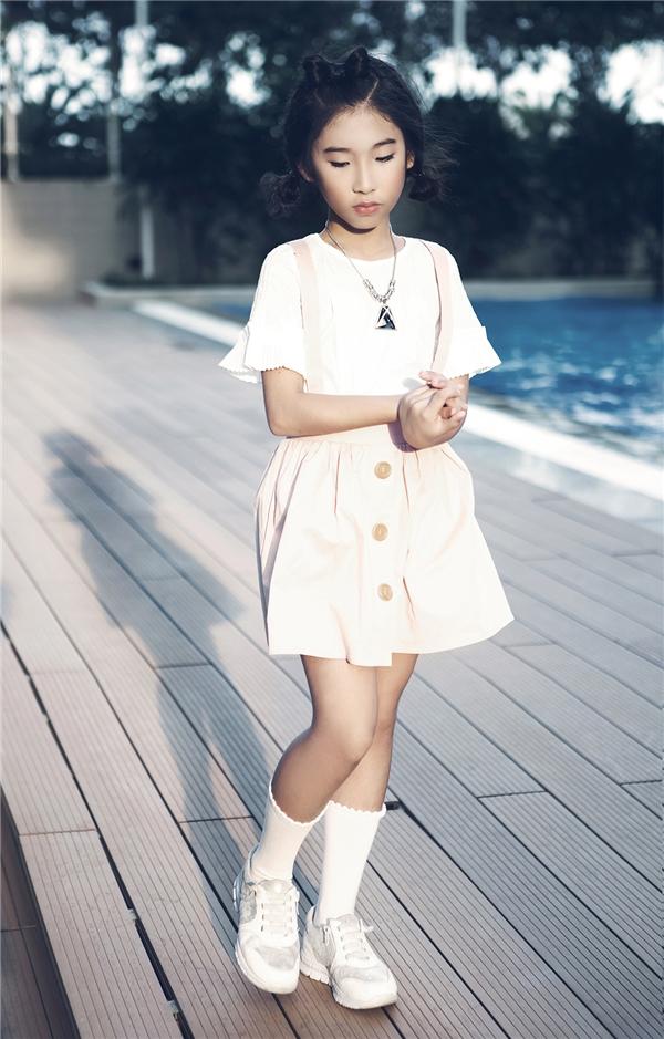 Bộ trang phục mang nét nữ tính, điệu đà lại được cô bé phối cùng giày thể thao mang màu sắc năng động, trẻ trung, cá tính.