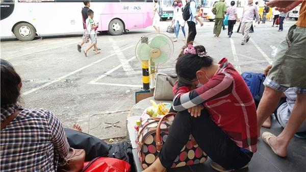Ngườiphụ nữ này kẹpđồ đạc tư trang vào lòng,tranh thủ ngủ một chúttrong lúc chờ xe tới.