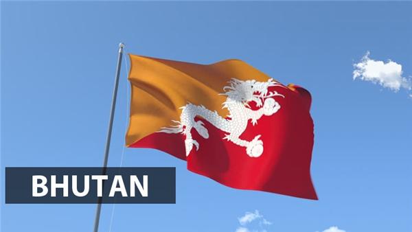 """Được biết đến với cái tên""""thần long chi quốc"""", quốc kỳ Bhutan nổi bật với biểu tượng con rồng trắng có bốn chân nắm bốn viên ngọc cùng màu ở trung tâm. Màu trắng tượng trưng cho sự thuần khiết và các viên ngọc là hiện thân của quyền lực tối cao."""