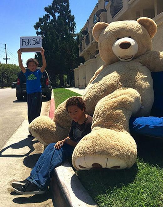2 cậu bé sinh đôi ngồi bán gấu trên vỉa hè.