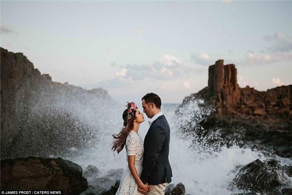 Cô dâu và chú rể say đắm nhìn nhau giữ con sóng cuồn cuộn tại Bombo Quarry, New South Wales, Úc.
