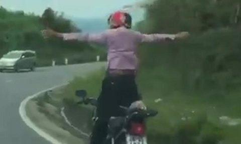 Nam thanh niên đứng lên, buông hai tay khi cho xe máy đổ dốc đèo. Ảnh: Cắt từ clip