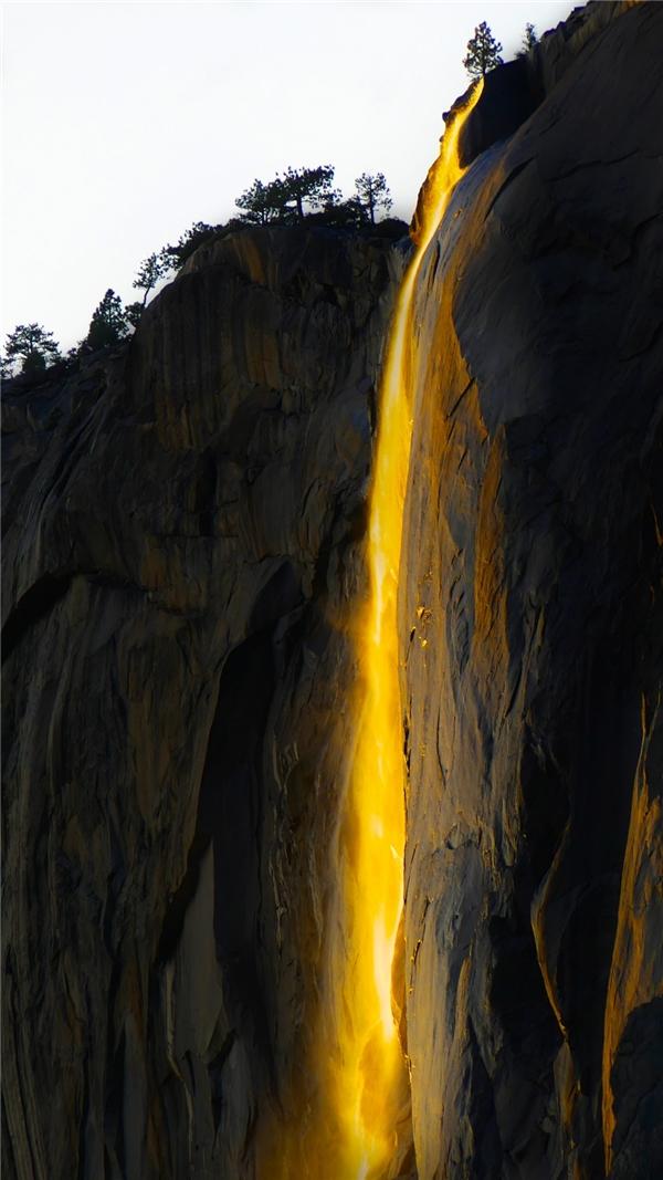 """Dòng """"thác lửa"""" hiện rõ trên vách núi khi Mặt Trời lặn dần."""