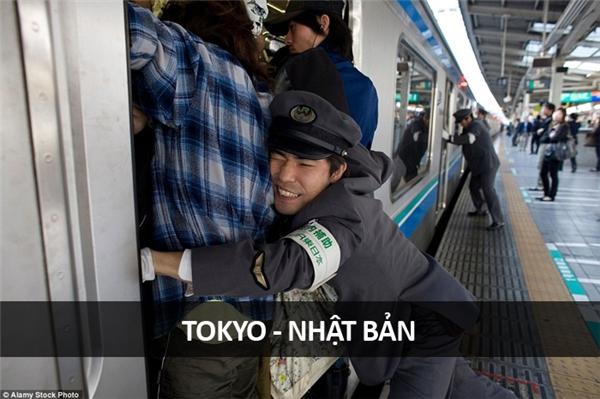 """Tại một ga tàu điện ngầm cực kì đông đúc ở Tokyo, các nhân viên nhà ga phải """"nhồi nhét"""" hành khách vào toa tàu trước khi tàu lăn bánh."""