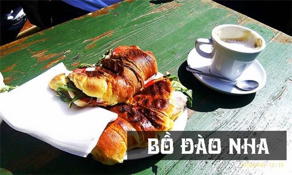 Người Bồ Đào Nha ăn bánh sừng bò kẹp thịt, rau và cà chua, dùng kèm một tách cà phê đánh bọt thơm ngonvào bữa sáng.