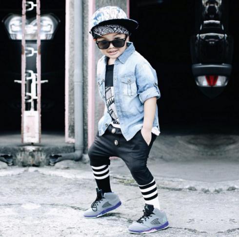 Cậu bé lựa chọn cho mình phong cách thời trang trưởng thành với áo sơ mi, quần jeans, giày loafer,...đi kèm cặp kính râm.