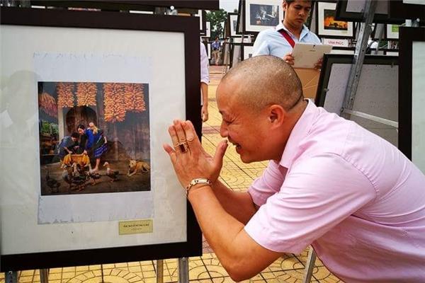 Một người xem tại triển lãm ảnh sáng nayhài hước khi chắp tayvái lạy tác phẩmvớiý chỉ trích sự giả dối. Ảnh: Ngọc Hà