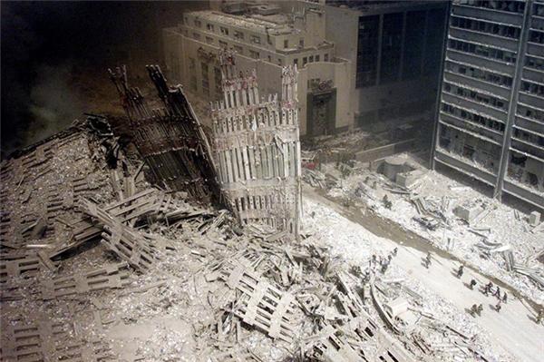 Một nhóm lính cứu hỏa bước giữa đống đổ nát gần nền móng của tòa tháp Nam đã bị phá hủy.