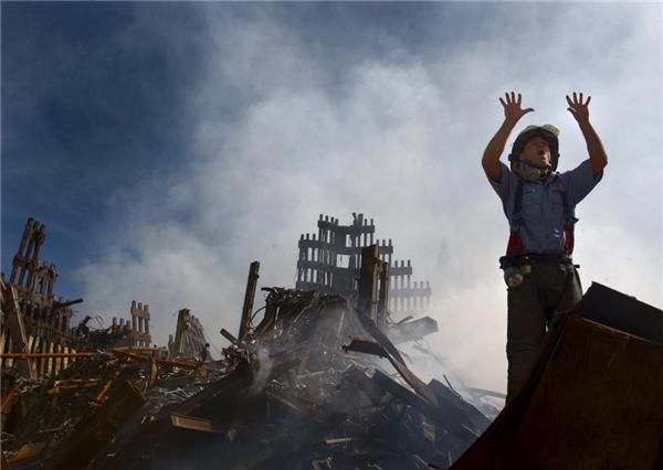 Một người lính cứu hỏa đang kêu gọi thêm đồng đội đến để len lỏi vào đống gạch vụn nhằm giải cứu những người may mắn còn sống.