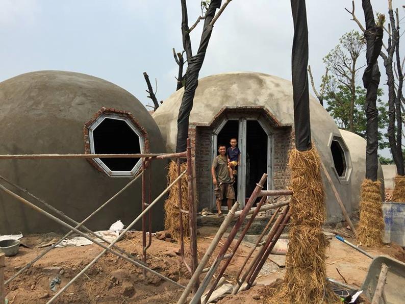 Anh Quỳnh và con trai trước ngôi nhà đang xây dang dở. (Ảnh: Theo Thanh niên)