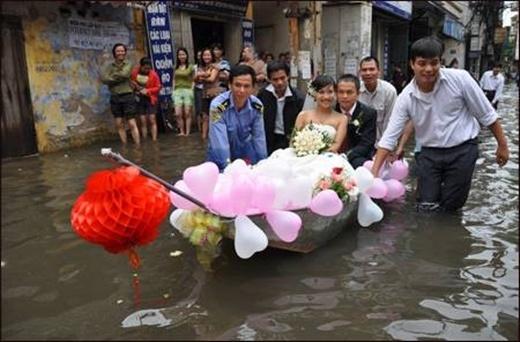 Mặc mưa gió bão bùng, cô dâu chú rểvẫn tươi cười hạnh phúc bên nhau.(Ảnh: Internet)