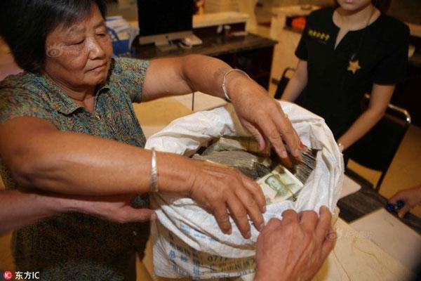 Cặp vợ chồng già đi mua nhà bằng... một bao tiền lẻ khổng lồ