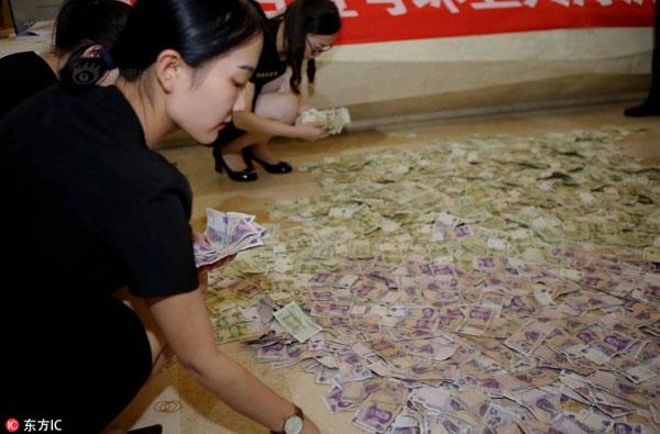 Toàn thể nhân viên công ty bất động sản được huy động để trải tiền xuống đất và tập trung đếm.