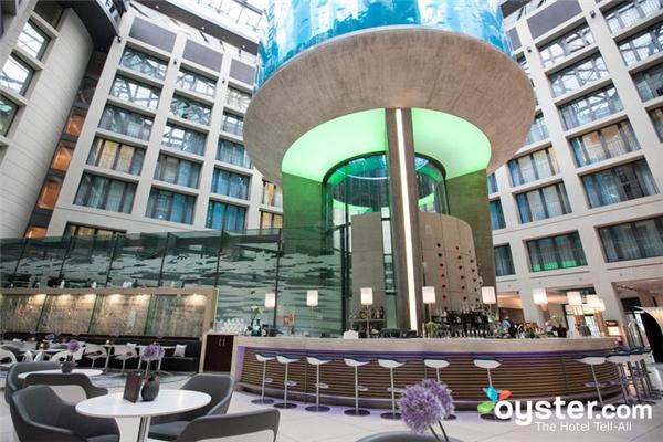 Nằm dưới bể cá hình trụ lớn nhất thế giới, Atrium Bar đặt ở sảnh khách sạn Radisson Blu ở Berlin, Đức. Tại đây, bạn sẽ được thưởng thức đồ uống và những món tráng miệng đồng thời ngắm bể cá thể tích 264.172 mét khối với hơn 1500 con cá. (Ảnh: Internet)