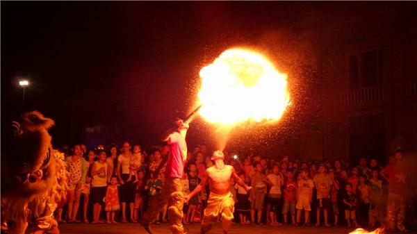 Khán giả đứngquanh đám biểu diễn múa lân thổi lửa. Ảnh: Mùa Xuân Dũng