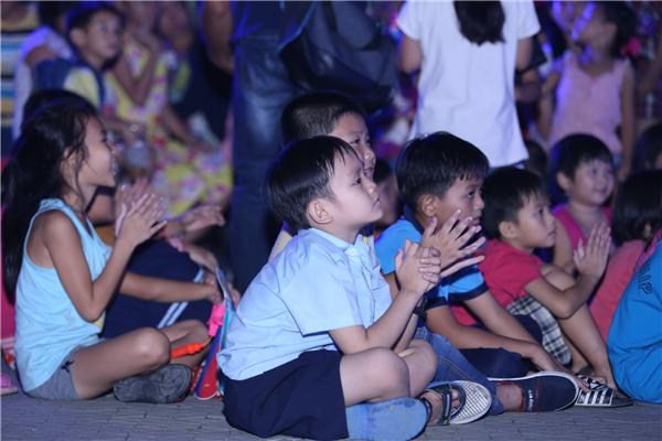 Các em chăm chú theo dõi các tiết mục biểu diễn trên sân khấu.