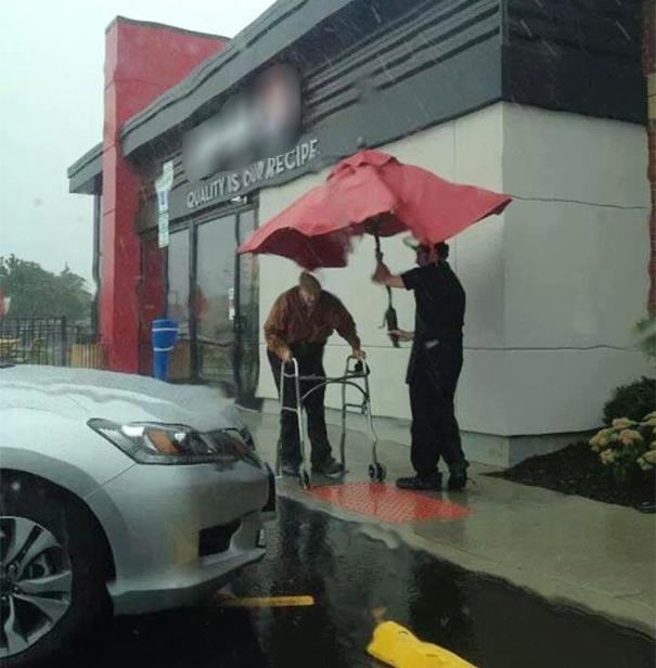 Một nhân viên cửa hàng rút chiếc ô từ bàn và chạy đến che cho cụ già đang di chuyển từng bước khó khăn trong mưa.