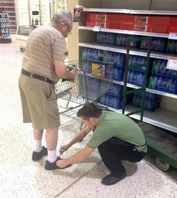 Nhân viên siêu thị cúi xuống buộc giày cho một cụ già.