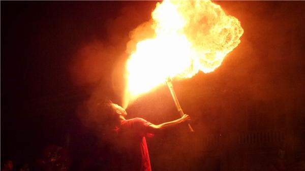 Ngậm dầu hỏa (hoặc xăng) phun mạnh vào ngọn đuốc, nguy cơ lửa béntheo luồng dung dịch làm cháy mặt cũng như quần áo rất cao. Ảnh: MùaXuân Dũng