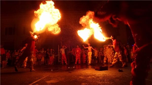 Xung quanh khu vực biểu diễn tiết mục nguy hiểm này là lân sư tử làm bằng giấy vàvải, những vật liệudễ gây cháy. Ảnh: Mùa Xuân Dũng