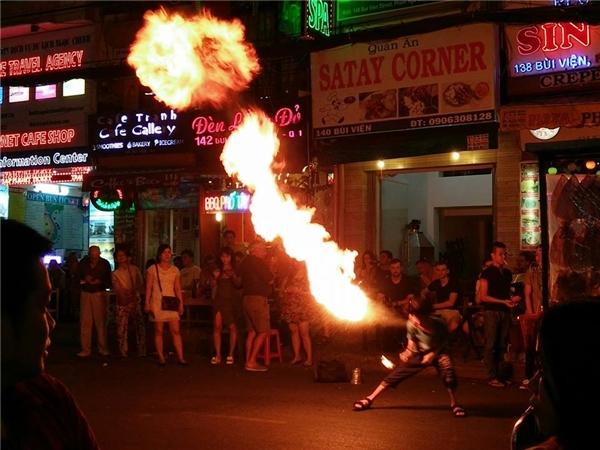 Tại TPHồ Chí Minh, khu phố Tây Bùi Viện nhỏ hẹp vớixung quanh là các hộ kinh doanh san sát tràn xuống cả vỉa hè,việc biểu diễn càng trở nênnguy hiểm. Lửa có thể bắt cháy vàodây điện và nhiều vậtdễ bénkhác. Ảnh: Joseph Phương