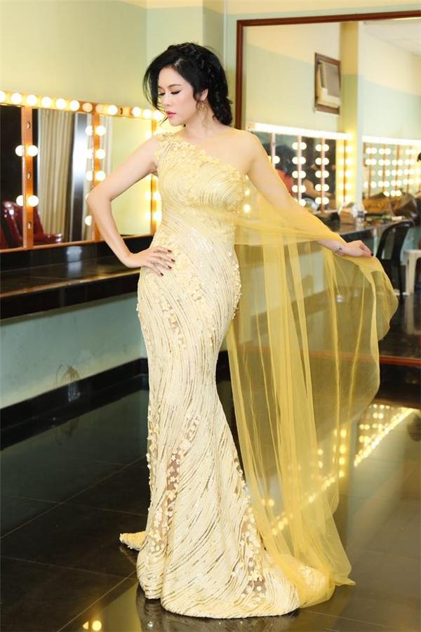 """Trong khi đó, Á hậu 1 Ngô Thanh Thanh Tú lại """"đụng hàng"""" với ca sĩ Thu Phương khi diện bộ váy vàng lệch vai ngọt ngào nhưng không kém phần gợi cảm."""