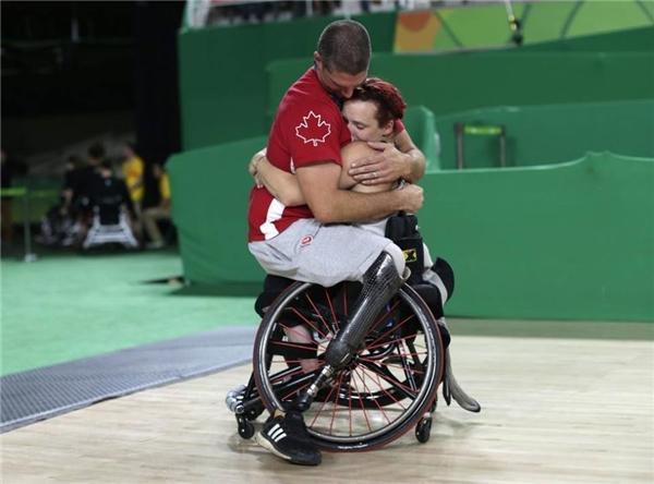 Adam Lancia, VĐV chơi cho độibóng rổ xe lăn namCanada ôm ngườivợ Jamey Jewellssau phần thi của cô ấy. (Ảnh:Ueslei Marcelino)
