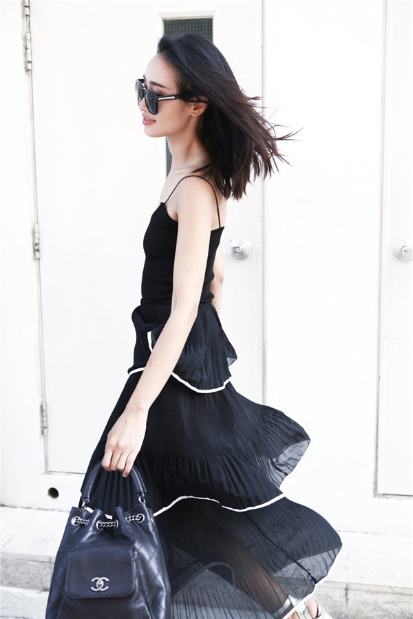 Thân hình cò hương của quán quân Vietnam's Next Top Model 2010 được khoe khéo qua chiếc áo 2 dây mỏng manh mang âm hưởng của phong cách thời trang váy ngủ. Kết hợp cùng chiếc áo là chân váy pleat đen có cấu trúc phân tầng mềm mại, mỏng manh.