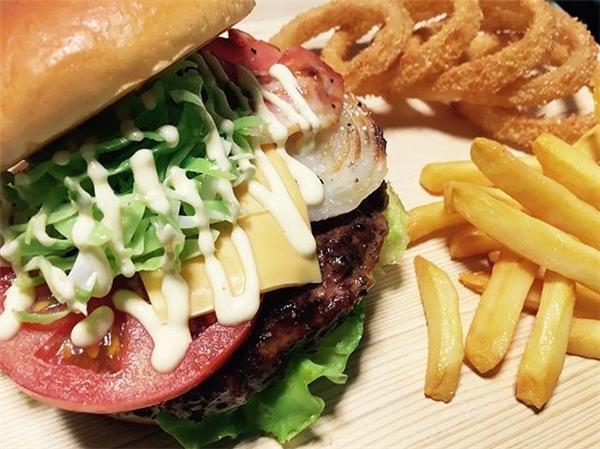 Chiếc bánhHamburger được sắp xếp cẩn thận với nhiều lớp rau, thịt nướng và phô mát xen kẽ.