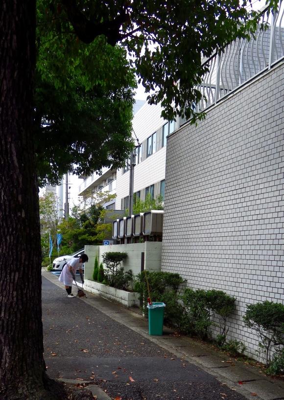 Một cô y tá ở Nhật đang quét dọn khu vực ngoài bệnh viện.