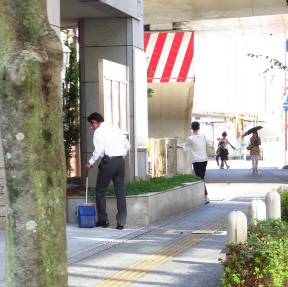 Một nhân viên văn phòng quét dọn khu vực trước công ty vào giờ trưa.