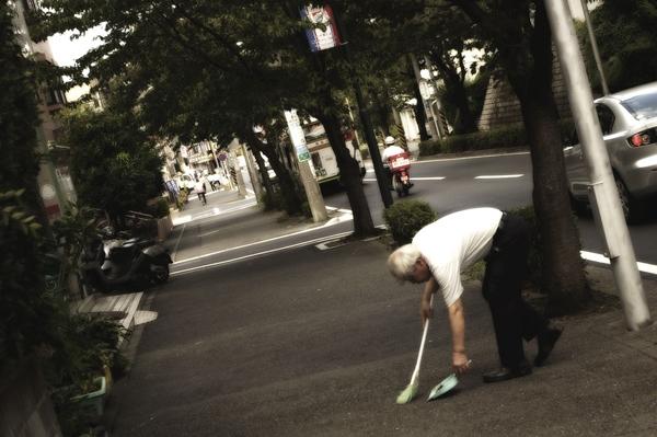 Một ông cụ người Nhật đang quét những mẩu giấy vụn rơi trên đường.