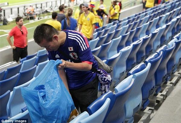 Thanh niên người Nhật dọn rác thải ở hàng ghế khán giảsau một trận cầu.