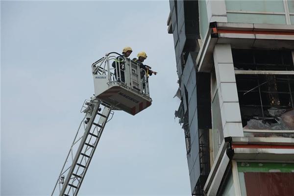 10h30p,ngọn lửa được kiểm soát. Cảnh sát PCCC tiếp cận hiện trường qua ô cửa kính bị vỡ trên tầng 5