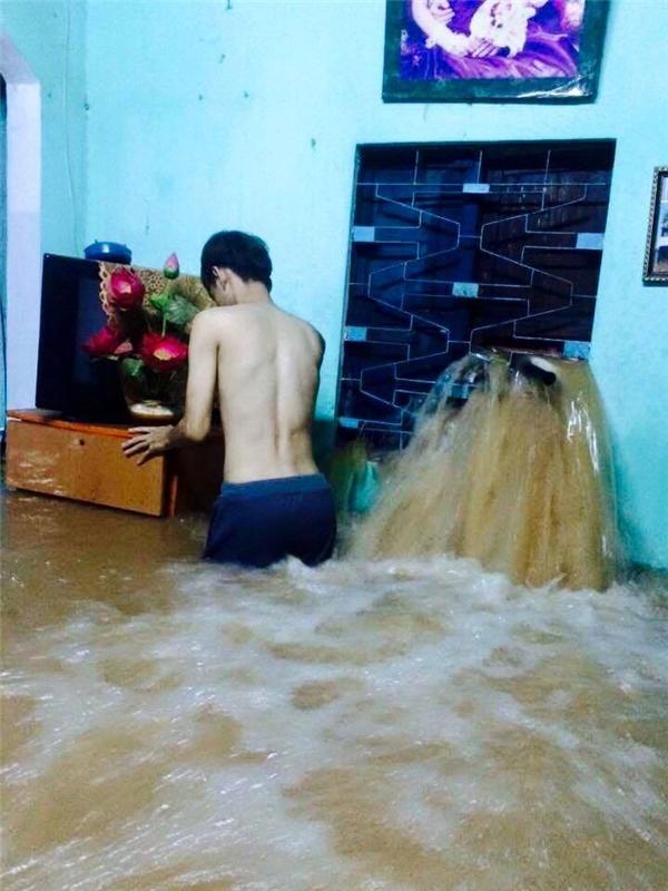 Nước tràn vào bằng cửa chính, nước làm thủngcửa sổ ào ạt ào nhà khiến người dân phải tìm cách di dời đồ đạc. (Ảnh: Internet)