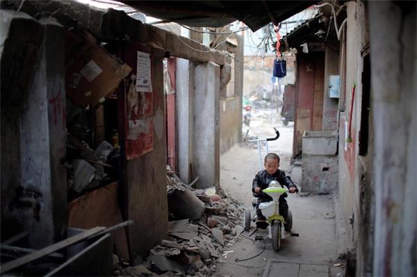 Một cậu bé lái xe trong những con ngõ nhỏ tại khu vực được ví như ổ chuột của Thượng Hải.