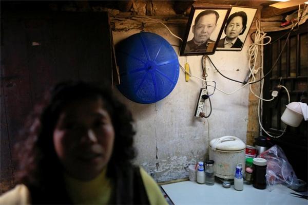 Người phụ nữ tên Li ngồi trong căn nhà của mình với di ảnh của bố mẹ chồng trên tường.