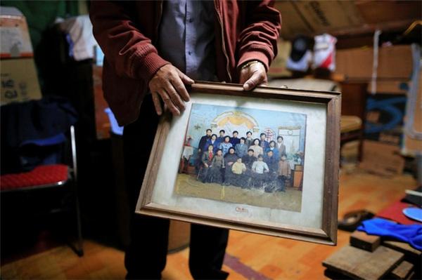 Người đàn ông tên Xu 50 tuổi với bức hình chụp đại gia đình. Cả nhà ông từng sống ở đây trước đó.